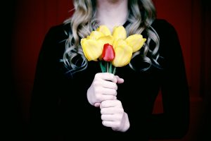 mujer con un ramo de flores amarillas y roja
