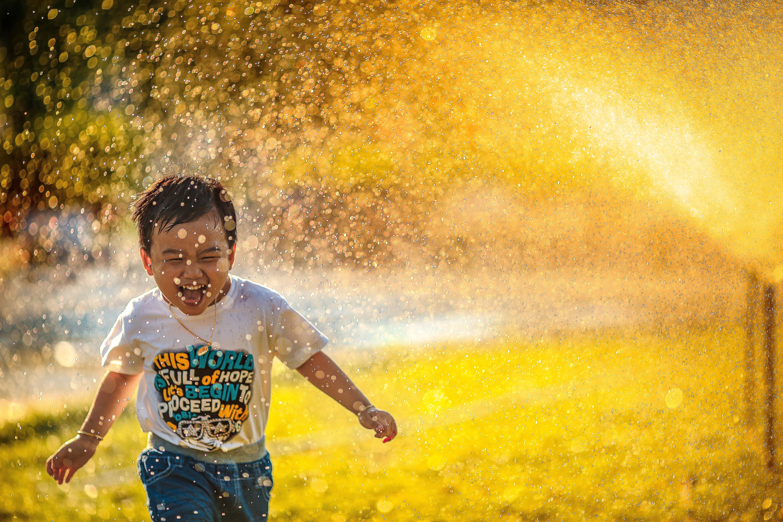 niño riendo ante una lluvia