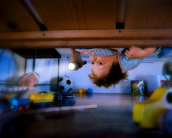Boy Checking Under Bed with Flashlight --- Image by © Bryan Allen/CORBIS