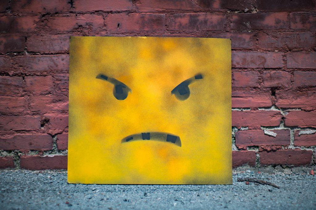 tablón amarillo con cara de enfado apoyado en la pared