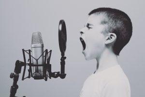 niño gritando a un micrófono de grabación