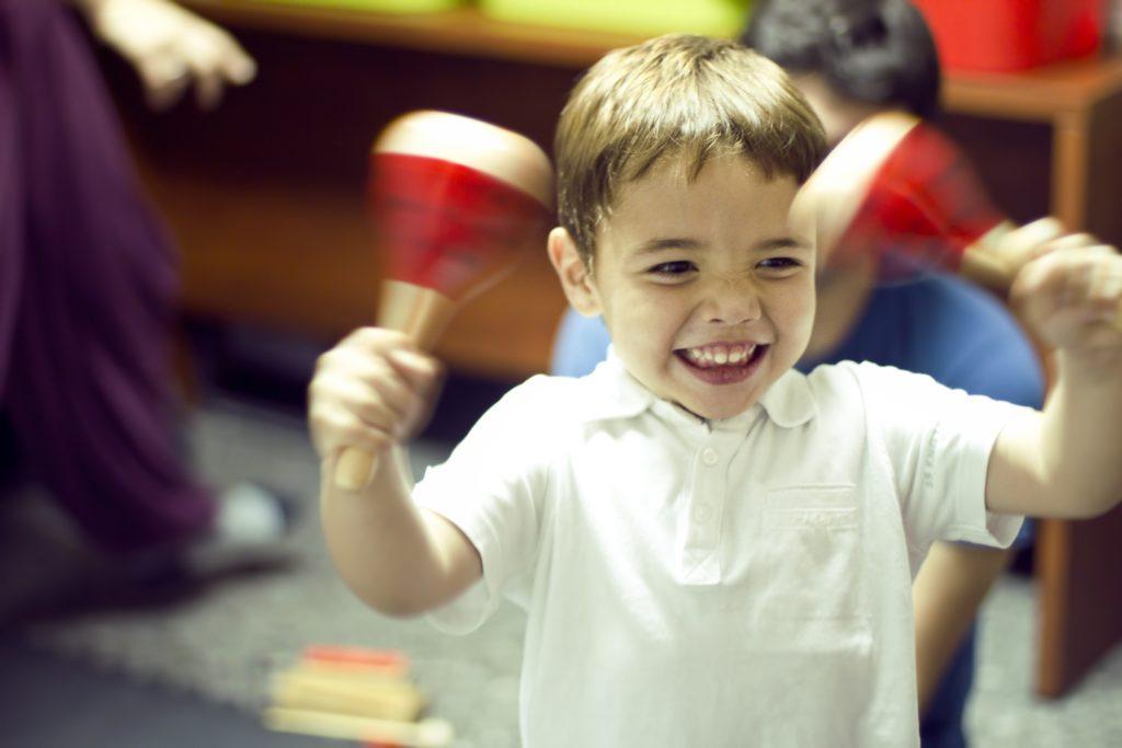 niños tocando maracas sonriendo