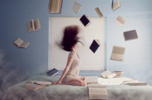 mujer con libros volando en la cama