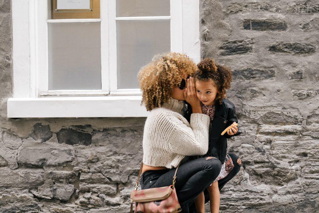 madre e hija hablando al oído en la calle