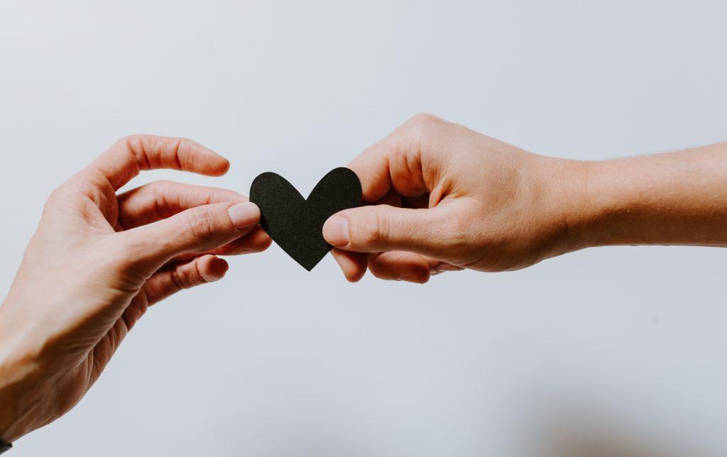 dos manos agarrando un corazón negro