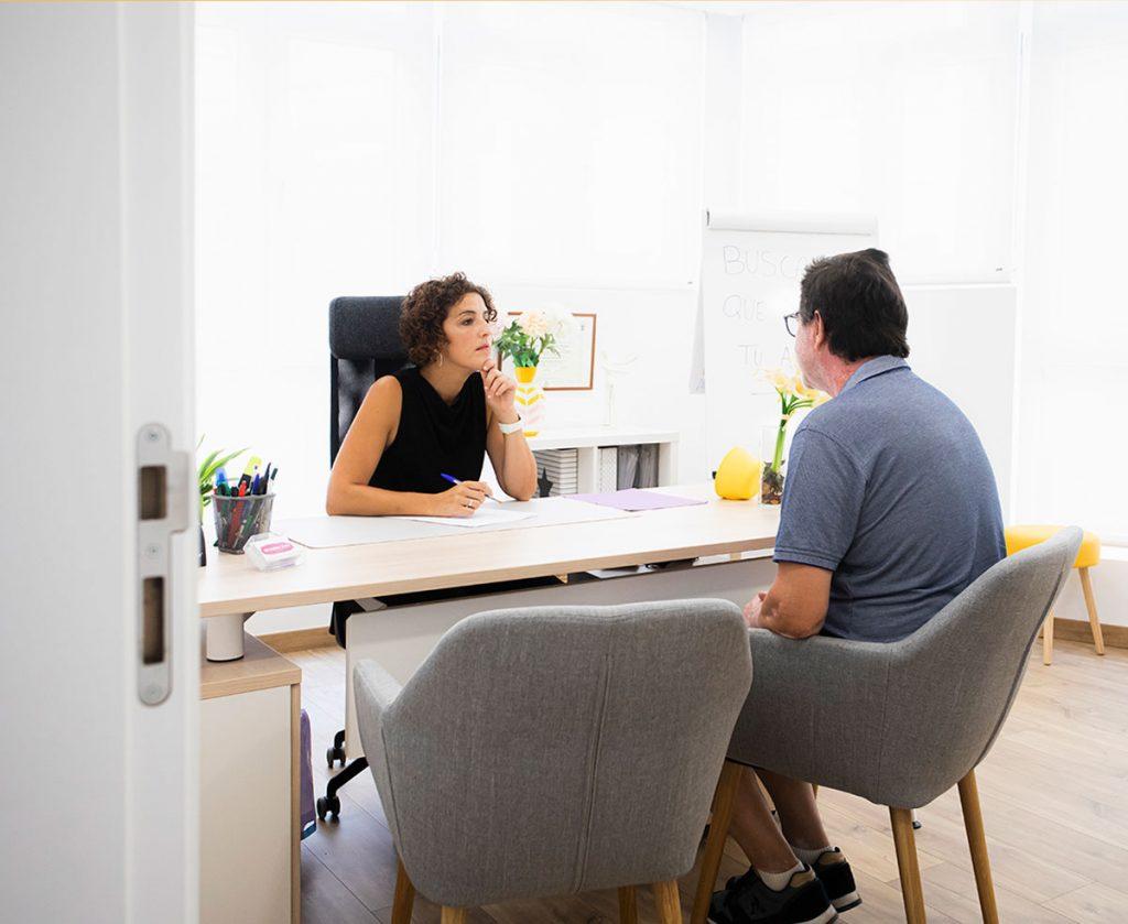 psicoterapeuta dando programa psicoeducativo con adulto en su despacho