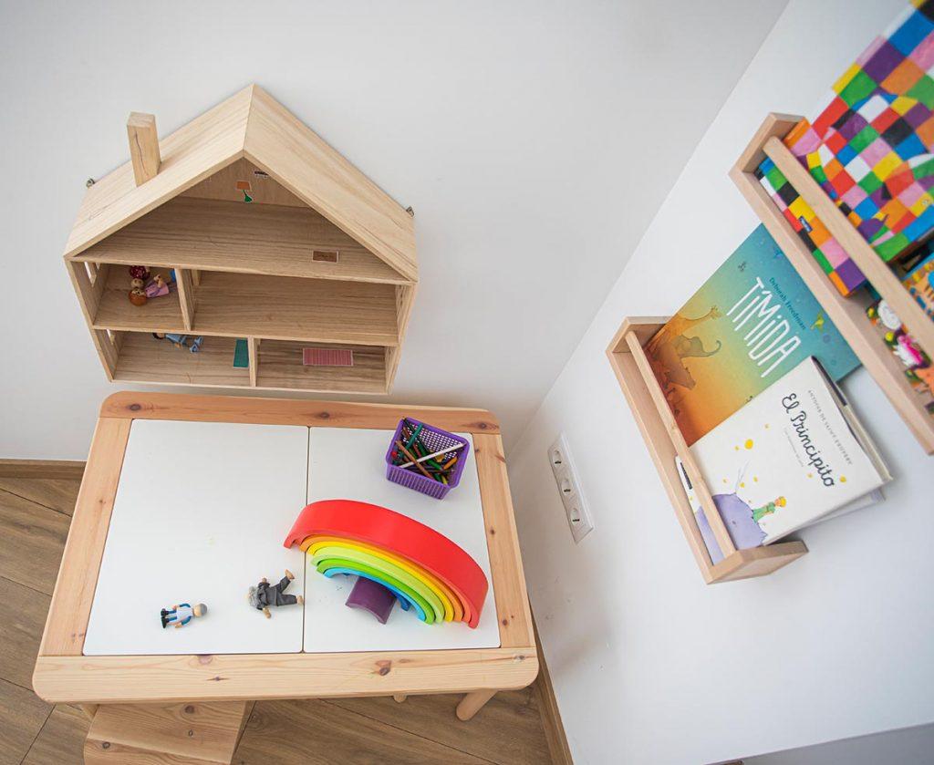 Rincón de la clínica hecho especialmente para niños donde hay un pupitre una silla una casita colgante en forma de estantería con muñecos en su interior, además de estanterías con cuentos