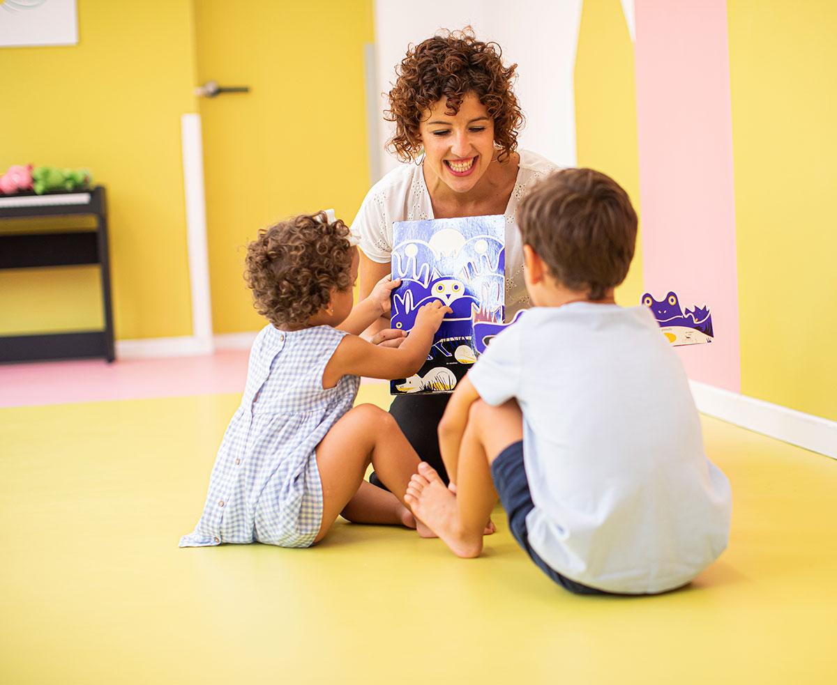psicologa sentada con dos niños mirando un cuento despelegable