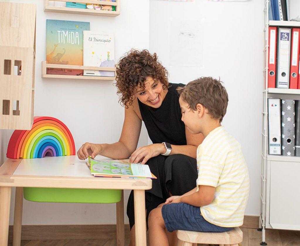 aida sentada con niño mirando un cuento