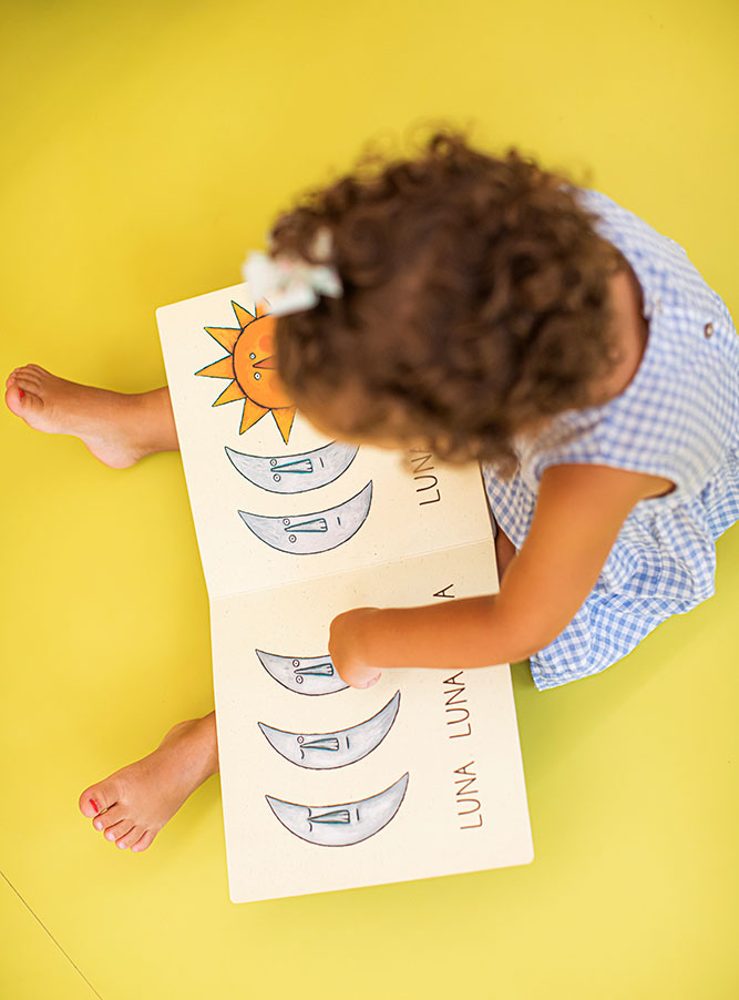 Niña pequeña sentada en suelo con libro