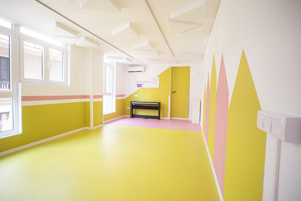 Sala muy grande y luminosa pintada de blanco amarillo pistacho, con mucha luz y con piano al fondo